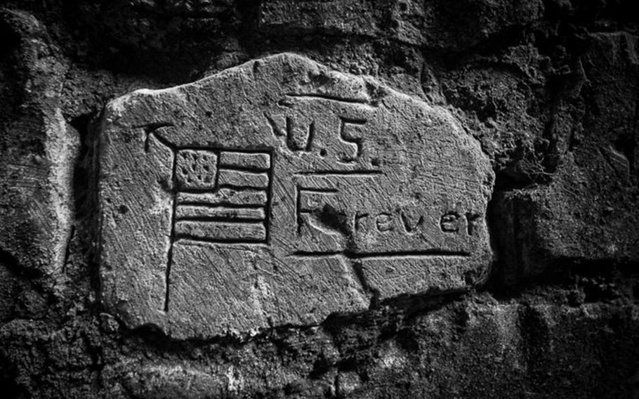 """An engraving left behind by U.S. soldiers from the 1st Division in France during WWI reads """"U.S. Forever."""" Photographed in January 2014, in Cantigny, France."""