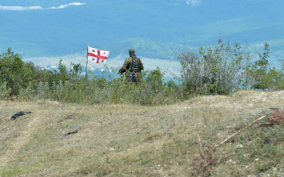 An armed man in uniform and wearing a mask stands near the Georgian flag on the boundary with the breakaway enclave of South Ossetia Thursday, July 16, 2015. Later, the flag was removed by a man who said he was a South Ossetian official.