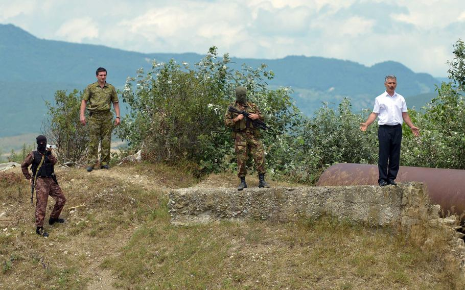 Robert Gasaev, right, who identified himself as deputy chief of the South Ossetia border control, surrounded by armed men who accompanied him, warns Georgian journalists to stay back after he removed a Georgian flag from what he said was South Ossetian territory, near Khurvaleti, Georgia, Thursday, July 16, 2015.