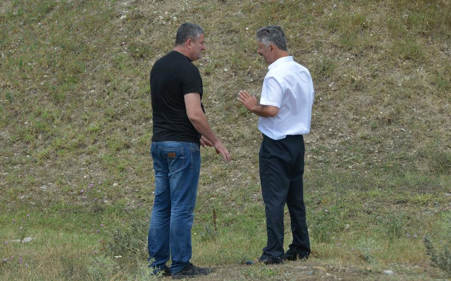 Davit Baidauri of the Georgian police, left, and Robert Gasaev,who identified himself as deputy chief of the South Ossetia border control, discuss the situation after Gasaev took down a Georgian flag that he said was on South Ossetian territory, near Khurvaleti, Georgia, Thursday, July 16, 2015.