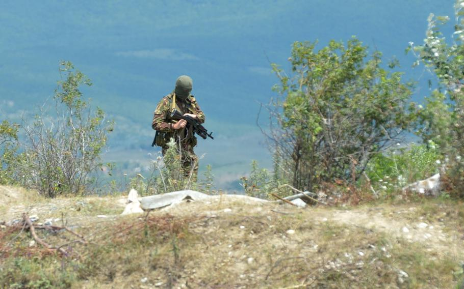 An armed man in uniform and wearing a mask near the boundary between the breakaway enclave of South Ossetia and Georgia, Thursday, July 16, 2015. A Georgian flag was removed on what the South Ossetians claimed was their territory.