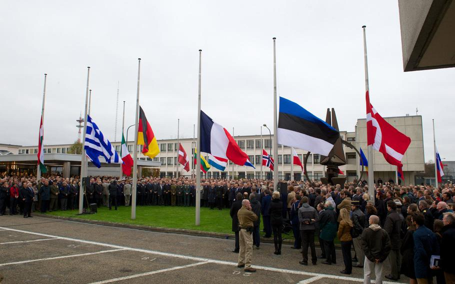 Staff members and others gather for a minute of silence at NATO Headquarters in Brussels on Monday, Nov. 16, 2015, in memory of the victims of the terrorist attacks in Paris.