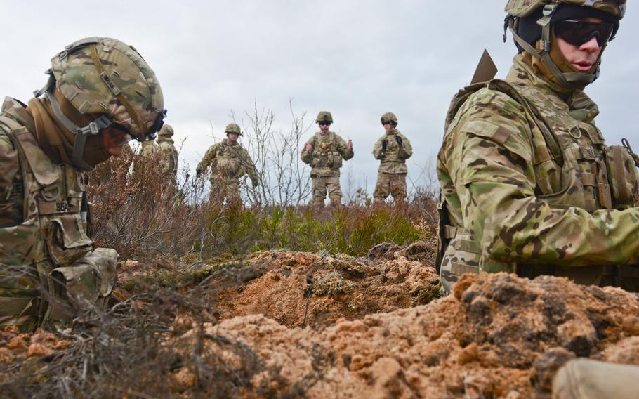 Soldiers of 3rd Squadron, 2nd Cavalry Regiment, stationed at Vilseck, Germany, stand in the trench and place dirt around the 43-pound charge craters to keep them stable so they can be buried in an upright position during a demolition training exercise at Adazi Training Area in Latvia, Jan. 30, 2016.