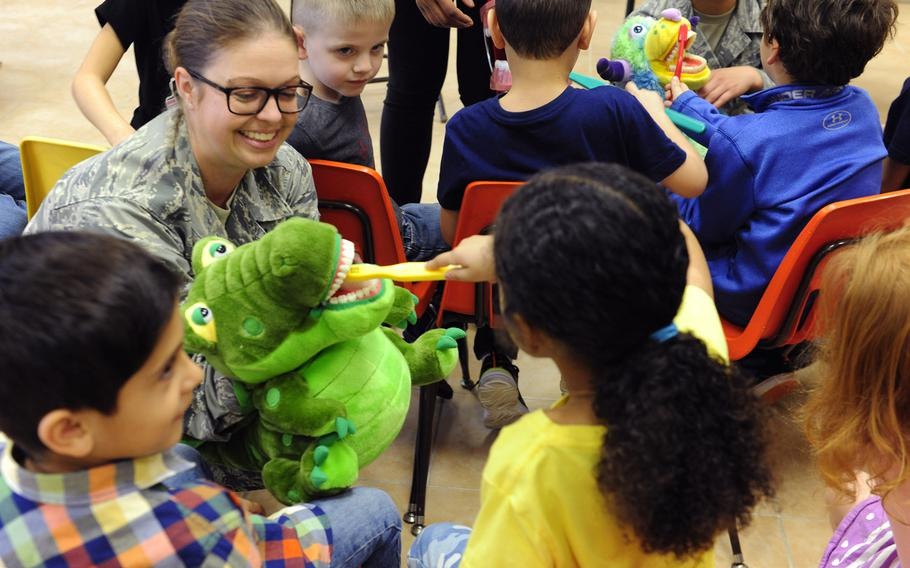 U.S. Air Force Master Sgt. Emily Jones, 39th Medical Operations Squadron dental flight chief, holds a puppet as children from the Incirlik Unit School demonstrate proper toothbrush technique Feb. 19, 2016, at Incirlik Air Base, Turkey. The Defense Department has announced on Tuesday, March 29, 2016, that it will start the evacuation all dependents, including some 270 schoolchildren, from the base for force-protection reasons.