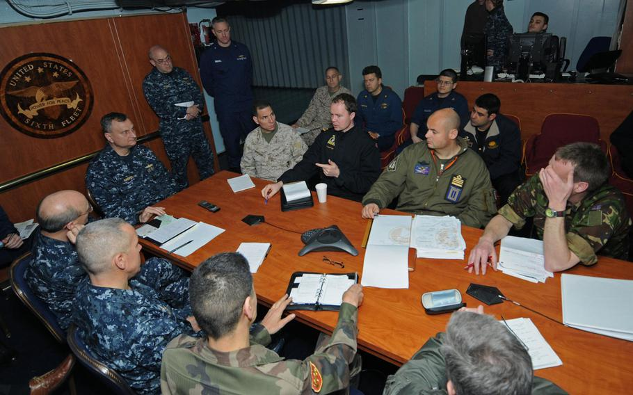 Liaison officers from coalition countries meet with Joint Task Force Odyssey Dawn staff members aboard the USS Mount Whitney in 2011 to discuss operations against the Libyan regime of Moammar Gaddafi.