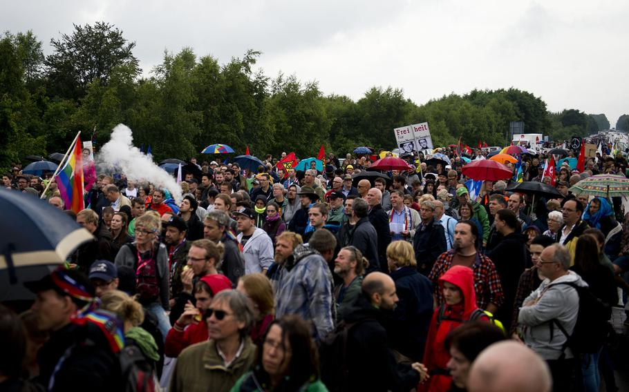 Protesters listen to a speaker outside Ramstein Air Base, Germany, on Saturday, June 11, 2016. Thousands of protesters converged in the rain outside the base to demand the facility end its alleged support of U.S. drone operations.