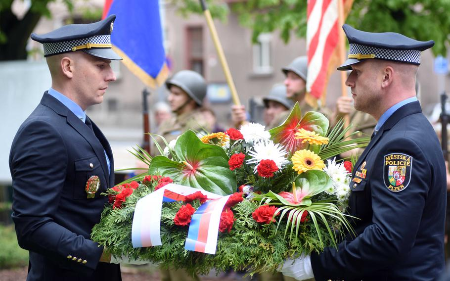 Police officers in Pilsen, Czech Republic, carry flowers to the city's monument to the American Army 2nd Infantry Division, Friday, May 5, 2017. The city of Pilsen annually celebrates the American liberation of their city in May.