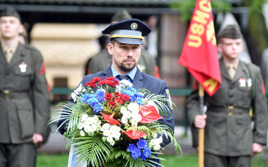 A Czech police officer carries flowers to a memorial to the American 2nd Infantry Division, during the Liberation Festival Pilsen, Friday, May 5, 2017. Behind him, re-enactors are dressed as U.S. Marines to honor the Marines who were originally part of the U.S. Army's 2nd Infantry Division.