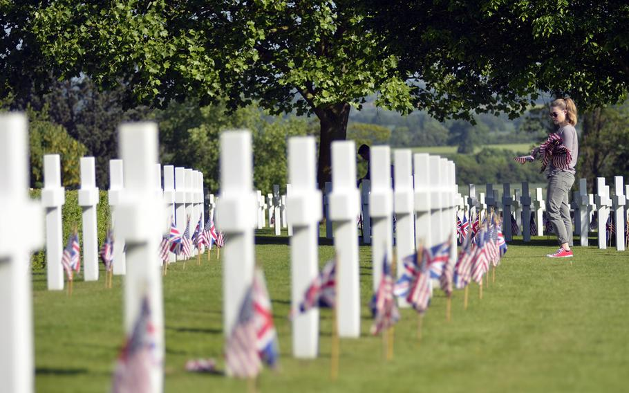 U.S. Air Force Airman 1st Class Brittany Holland places U.S. flags near headstones at the Cambridge American Cemetery and Memorial in Cambridge, England, Friday, May 26, 2017, in preparation for this Memorial Day.