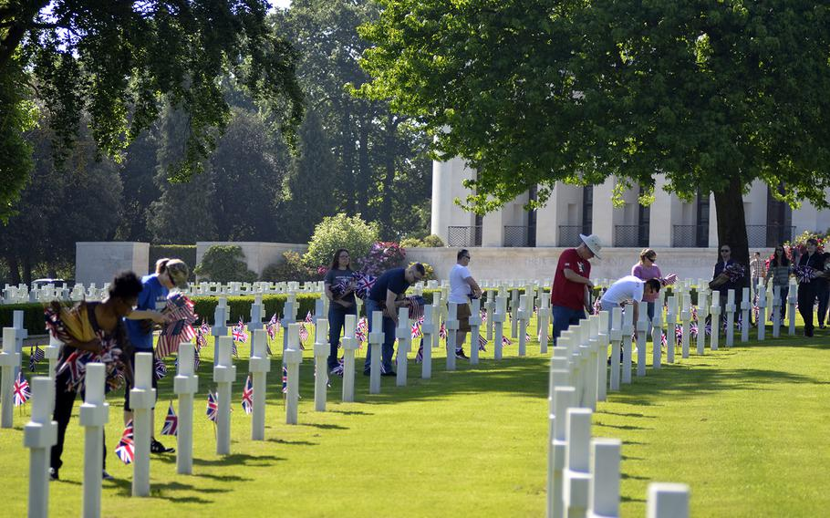 Volunteer U.S. servicemembers, veterans and the local British community members place flags among headstones at the Cambridge American Cemetery and Memorial in Cambridge, England, Friday, May 26, 2017, in preparation for this Memorial Day.