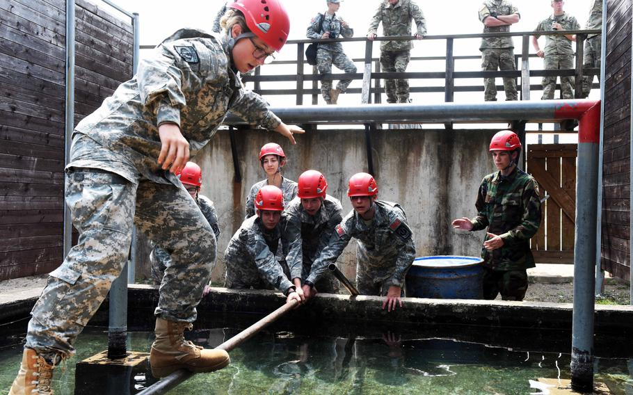 JROTC cadets carefully maneuver an obstacle at the leadership reaction course, Thursday, June 22, 2017, at Grafenwoehr, Germany.
