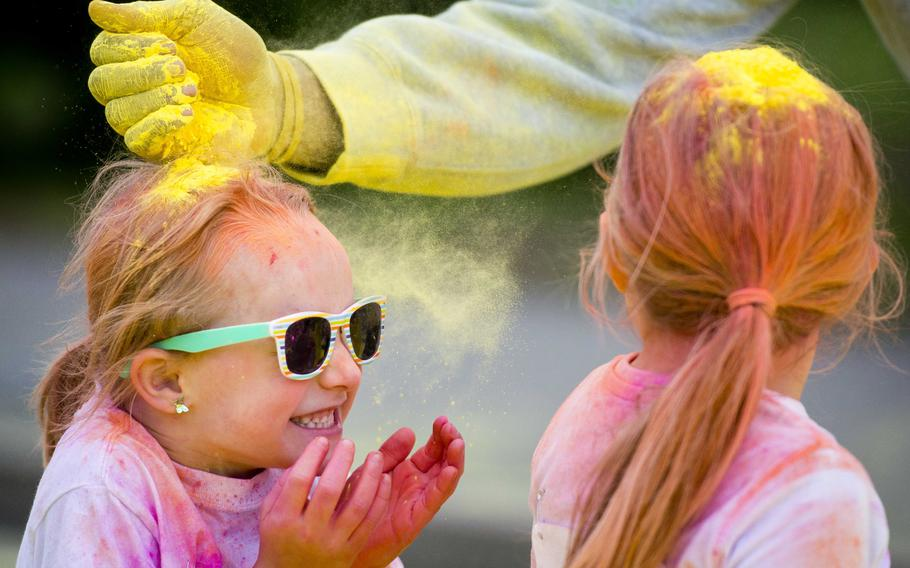 Girls get a gift of colored powder on their heads during the annual Color Run at Ramstein Air Base, Germany, on Saturday, Aug. 12, 2017.