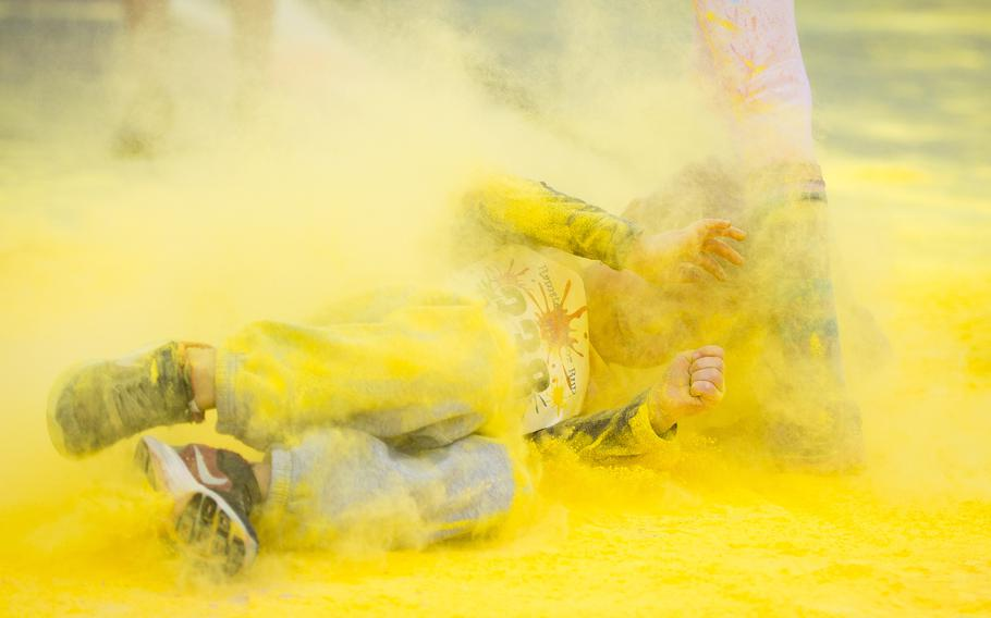 A boy rolls through colored powder during the annual Color Run at Ramstein Air Base, Germany, on Saturday, Aug. 12, 2017.