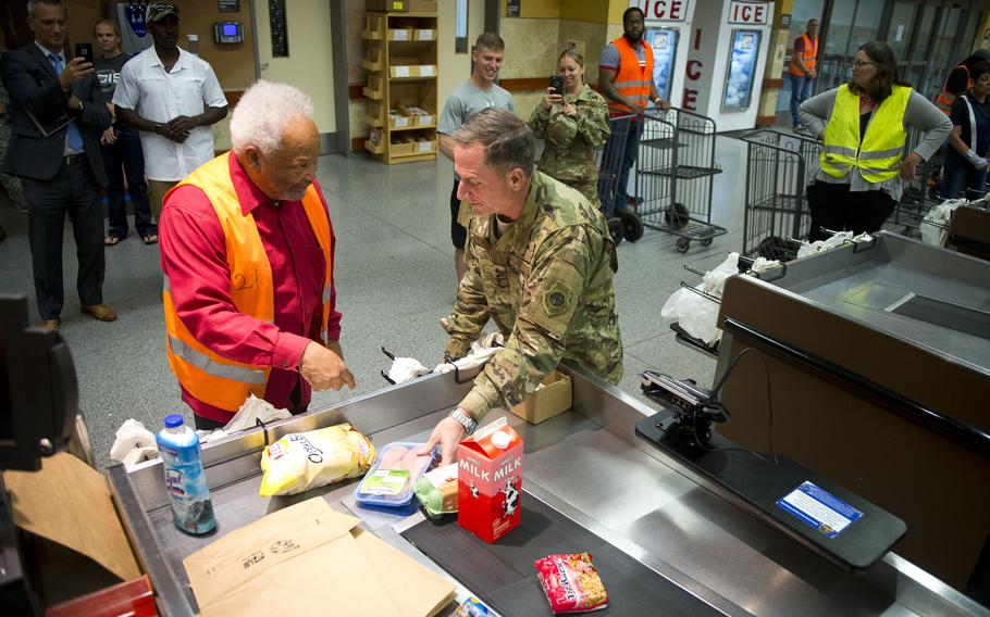 Air Force Chief of Staff Gen. David Goldfein, right, and Charlie Searchwell bag groceries at Ramstein Air Base, Germany, on Monday, Aug. 21, 2017. When Goldfein was a teenager he bagged groceries for Searchwell at the commissary.