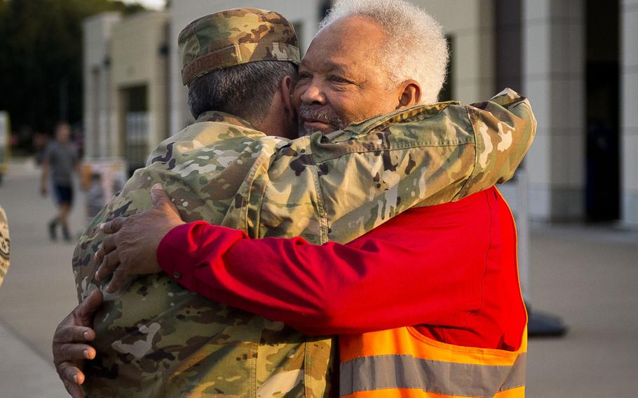 Charlie Searchwell, right, and Air Force Chief of Staff Gen. David Goldfein hug in front of the commissary at Ramstein Air Base, Germany, on Monday, Aug. 21, 2017. Searchwell was Goldfein's first boss when he bagged groceries as a teenager.