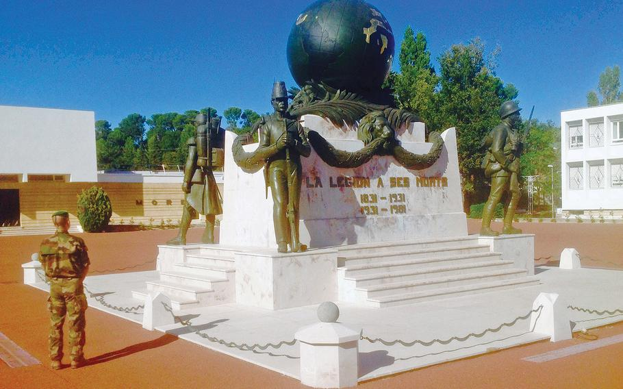 A legionnaire stands in front of the Foreign Legion's monument to the dead, on the parade ground at Aubagne, the unit's headquarters and its main recruitment base. The monument, which was originally built at the Legion's base in Algeria, was dismantled and rebuilt in Aubagne in the 1960s after the end of French colonial rule in that North African nation.