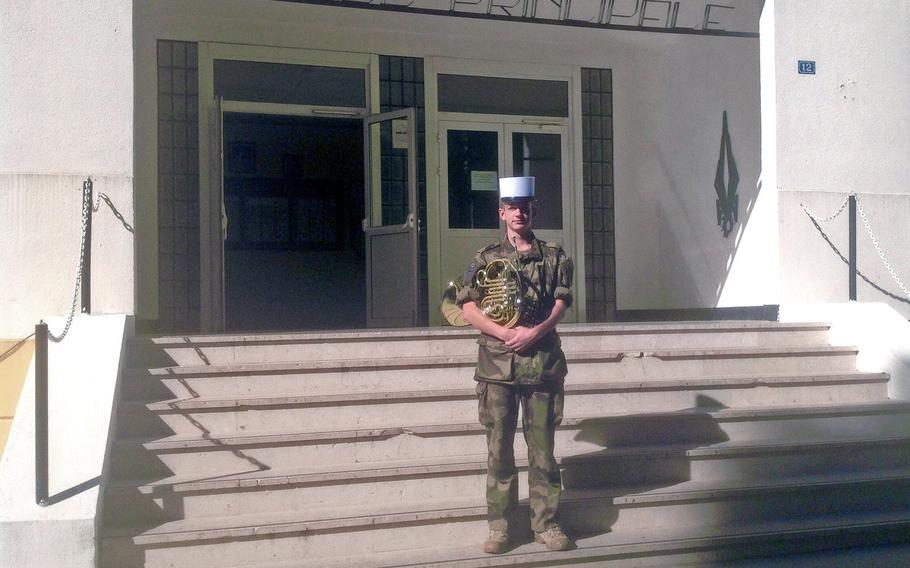 """Timothy Cool, an American serving in the French Foreign Legion, stands in front of the building housing the Legion's marching band. The 27-year-old from Menash, Wis., is completing his five-year of duty and has already re-upped. """"We're musicians but we're also combat soldiers - not just pretend soldiers,"""" he said."""