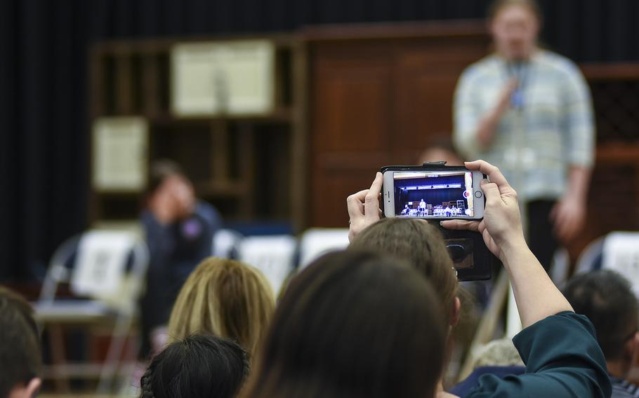 An audience member records with her phone while Sara Moriarity of Naples High School spells a word during the 35th Annual European PTA Spelling Bee on Saturday, March 10, 2018, at Ramstein Air Base, Germany. Moriarity finished third in the contest.