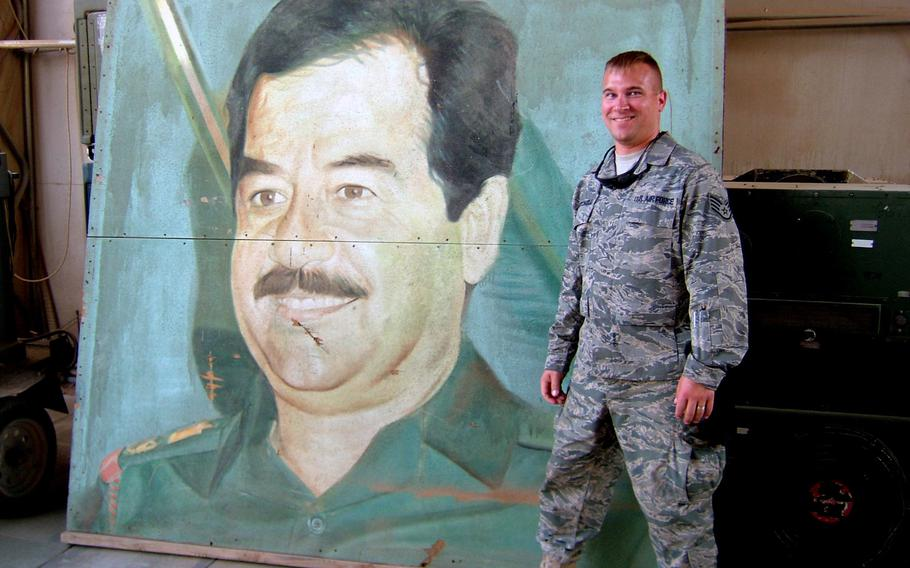 Master Sgt. Jerred Mitchell stands next to a painting of the late former Iraqi president Saddam Hussein while deployed to Iraq in 2008. Mitchell deployed four times during his military career, including twice to Iraq for Operation Iraqi Freedom.