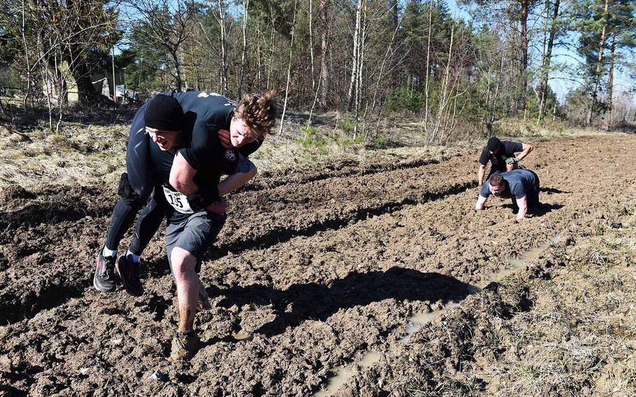 Runners attempt to carry each other across a muddy track during the Rugged Terrain Obstacle Run at Grafenwoehr, Germany, Saturday, April 7, 2018.