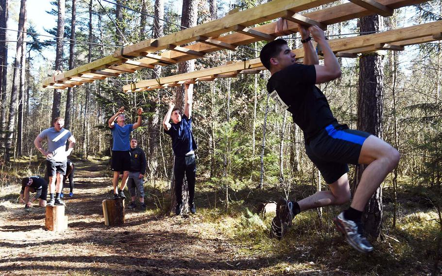 Runners maneuver through the monkey bars during the Rugged Terrain Obstacle Run, at Grafenwoehr, Germany, Saturday, April 7, 2018.