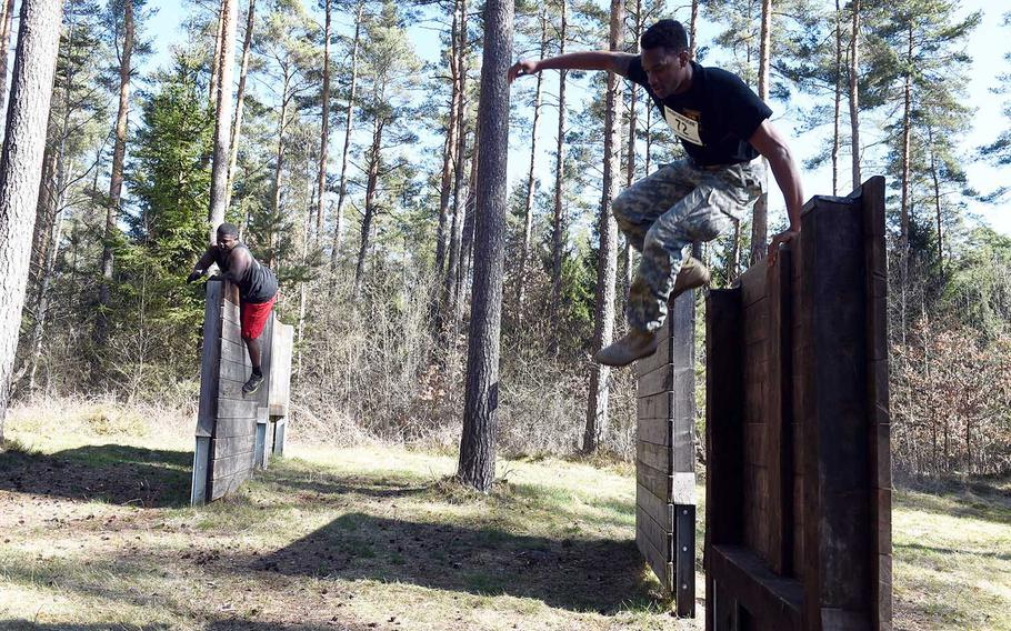 Runners jump over walls during the Rugged Terrain Obstacle Run, at Grafenwoehr, Germany, Saturday, April 7, 2018.