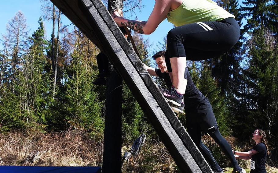 Runners use ropes to climp to the top of an obstacle during the Rugged Terrain Obstacle Run, at Grafenwoehr, Germany, Saturday, April 7, 2018.