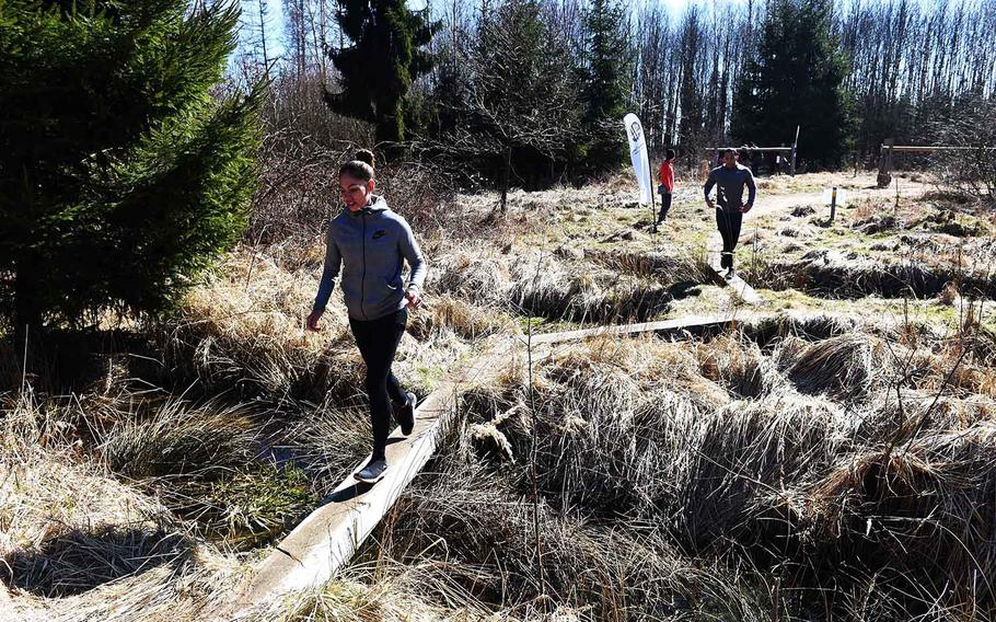 Runners race through a zig-zag of logs during the Rugged Terrain Obstacle Run, at Grafenwoehr, Germany, Saturday, April 7, 2018.