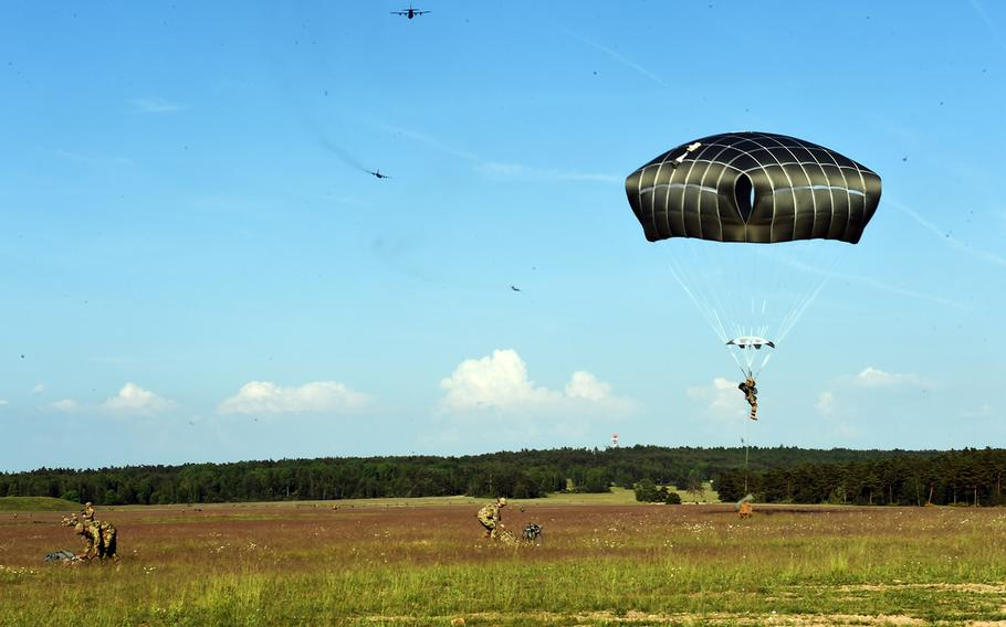 Paratroopers with the 173rd Brigade Combat Team (Airborne) drop down and ready their gear for an artillery live-fire exercise at Grafenwoehr, Germany, Friday, May 18, 2018.