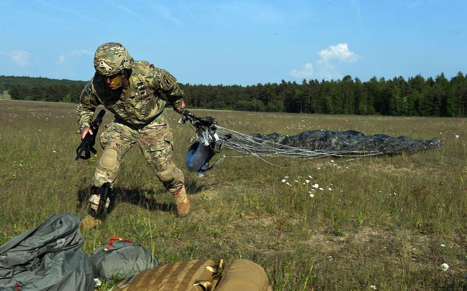 Maj. Michael Centola, executive officer of the 4-319 Field Artillery Regiment, part of the 173rd Brigade Combat Team (Airborne), pulls his parachute toward his pack during a live-fire artillery exercise at Grafenwoehr, Germany, Friday, May 18, 2018.