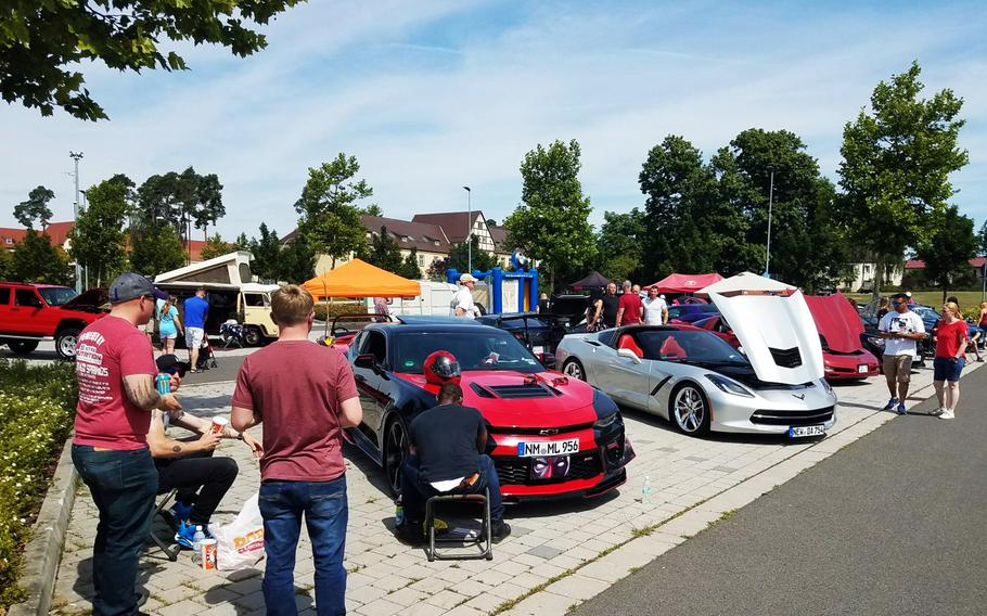 Soldiers and families check out cars on display at the Independence Day car show at Grafenwoehr, Germany, Wednesday, July 4, 2018.
