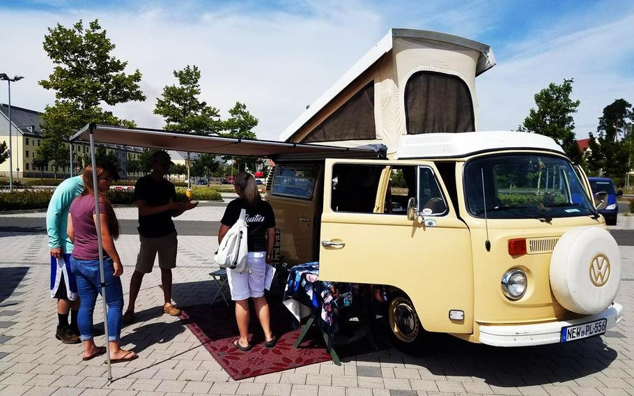 Soldiers and families check out a Volkswagen bus at the Independence Day car show put on by the Better Opportunities for Single Soldiers program, at Grafenwoehr, Germany, Wednesday, July 4, 2018.