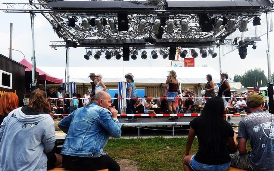 Germans and Americans try line dancing at the German-American Volksfest at Grafenwoehr, Germany, Friday, Aug. 3, 2018.
