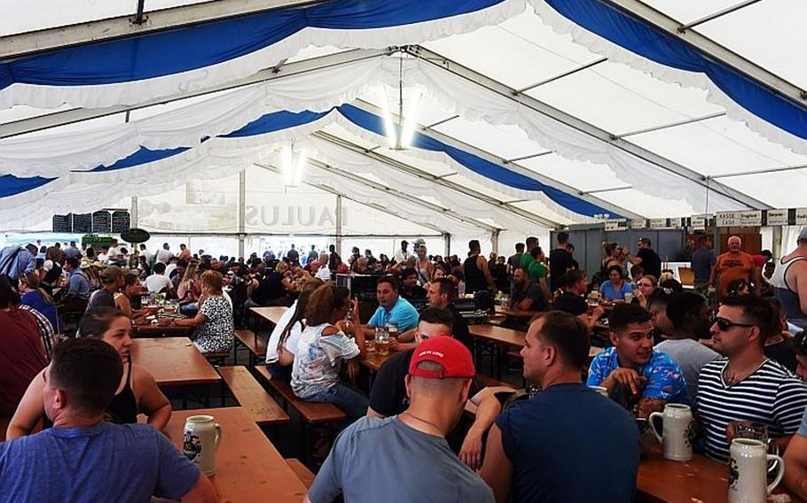 Germans and Americans drink beer under a German-style beer tent at the German-American Volksfest at Grafenwoehr, Germany, Friday, Aug. 3, 2018.
