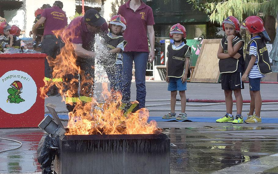 Firefighters with the Vigili del Fuoco of Pordenone help a child put out a mock fire during the 17th annual Italian-American Frienship Festival that took place Saturday, Sept. 8, 2018, in the city of Pordenone, Italy.