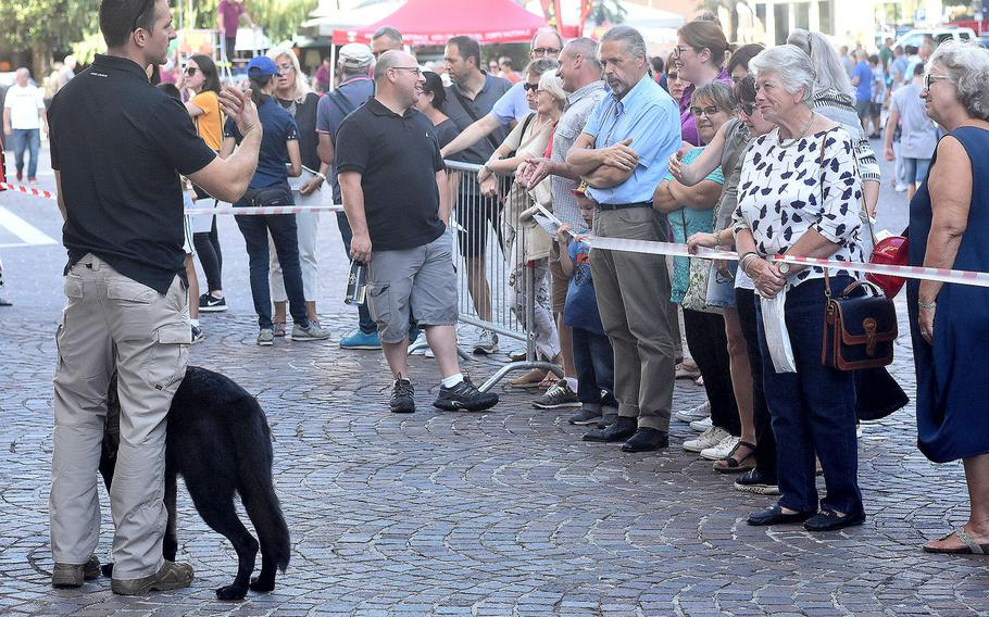 An member of the canine unit of the 31st Fighter Wing's security forces, Aviano Air Base, Italy, addresses a group of people during a military working dog demonstration that was held at the XX Settembre piazza, Pordenone. The demonstration was part of the 17th annual Italian-American Friendship Festival that took place Saturday, Sept. 8, 2018, in the city of Pordenone.