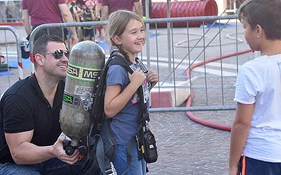 A firefighter with the 31st Fighter Wing fire department helps a child try on a small fire fighters' oxygen tank during the 17th annual Italian-American Frienship Festival that took place Saturday, Sept. 8, 2018, in the city of Pordenone, Italy.