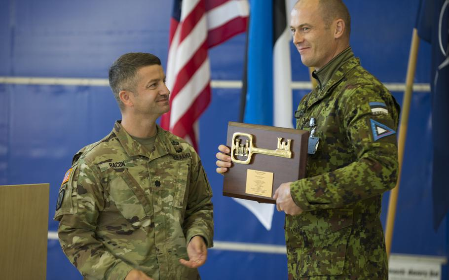 Lt. Col. John Bacon, U.S. Army Corps of Engineers division deputy commander, hands the ceremonial key to the newly completed aircraft maintenance facility to Lt. Col Ülar Lõhmus, Estonia's Amari Air Base commander, Oct. 16, 2018.