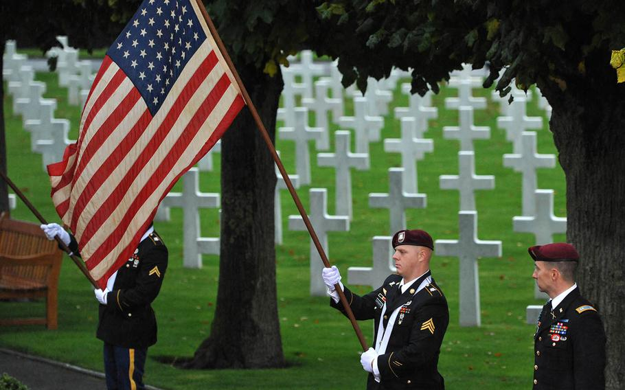 A U.S. Army soldier holds the American flag during the World War I armistice centennial ceremony, at Suresnes American Cemetery  Sunday, Nov. 11, 2018.