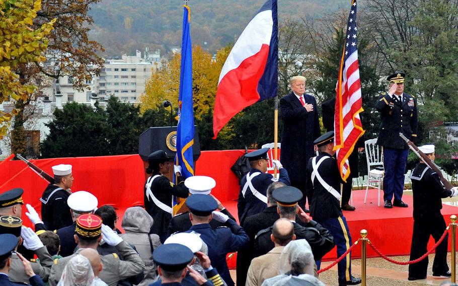President Donald Trump is framed by the U.S. and French flags of the U.S. European Command color guard as they present the colors at the start of the World War I armistice centennial ceremony, at Suresnes American Cemetery  Sunday, Nov. 11, 2018.