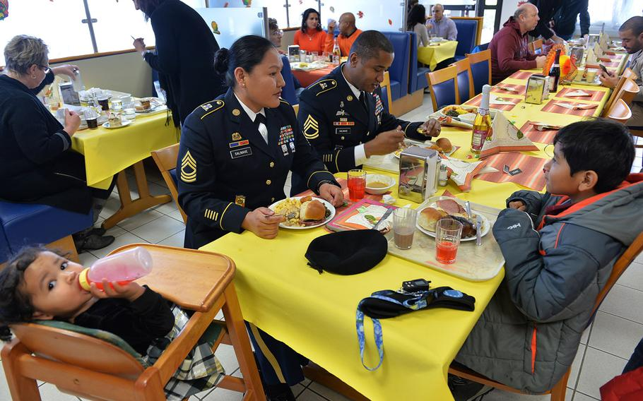 The Salnaves, Sgt. 1st Class Stephane Salnave his wife Master Sgt. Karie Salvane, eat Thanksgiving Dinner with their infant daughter and son at the Clock Tower Cafe dinning facility on Kleber Kaserne in Germany.