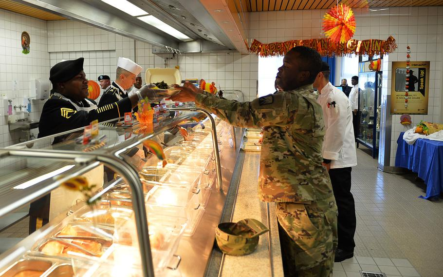 Staff Sgt. Terrell Price picks up a carryout container and returns to duty on Thanksgiving Day at Kleber Kaserne in Germany.