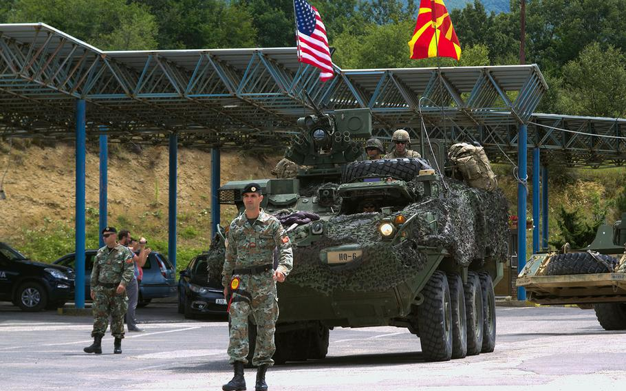 A U.S. Army Stryker is guided across the Macedonian border by a Macedonian soldier at the Deve Bair border station in 2017. Macedonia was formally invited Wednesday to join  NATO.