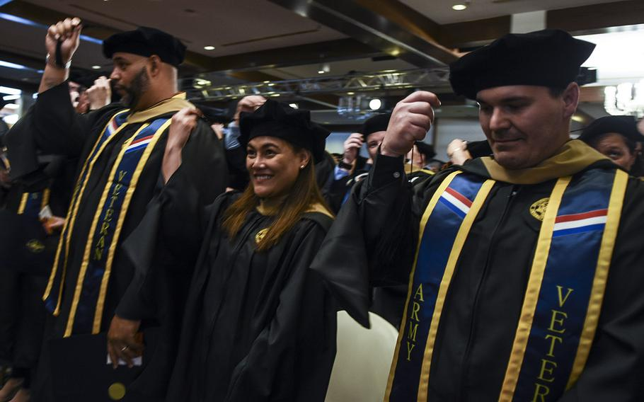 Graduates move their cap tassels from right to left after receiving their diplomas at the UMUC Europe commencement on Saturday, May 4, 2019, at Ramstein Air Base, Germany.