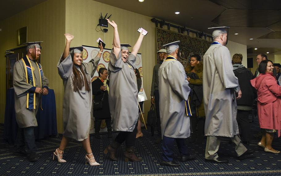 UMUC Europe graduates celebrate while lining up for commencement on Saturday, May 4, 2019, at Ramstein Air Base, Germany.