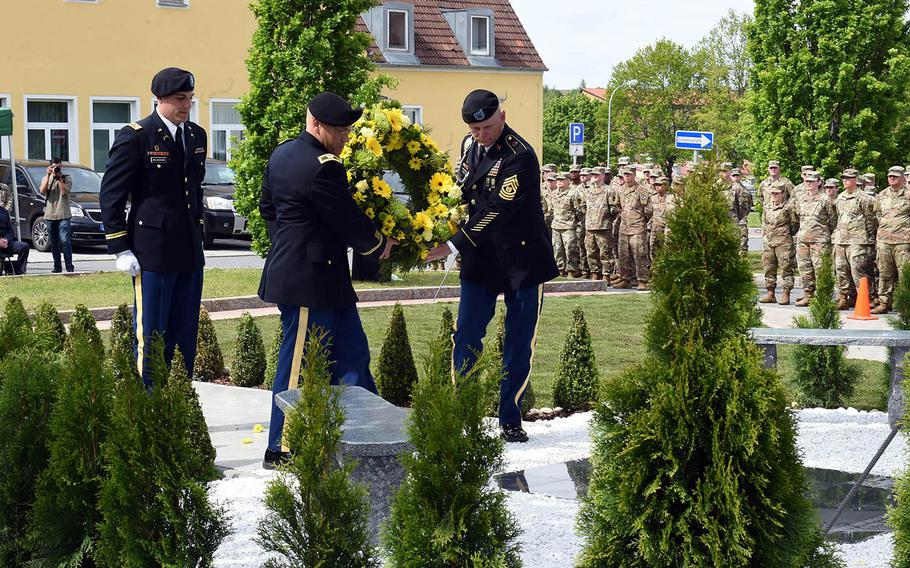 Sgt. Maj. Ted Pearson and Col. Glenn Schmick, with the 18th Military Police Brigade, carry a wreath to the newly rededicated memorial to fallen soldiers from their brigade, Thursday, May 23, 2019, at Vilseck, Germany.