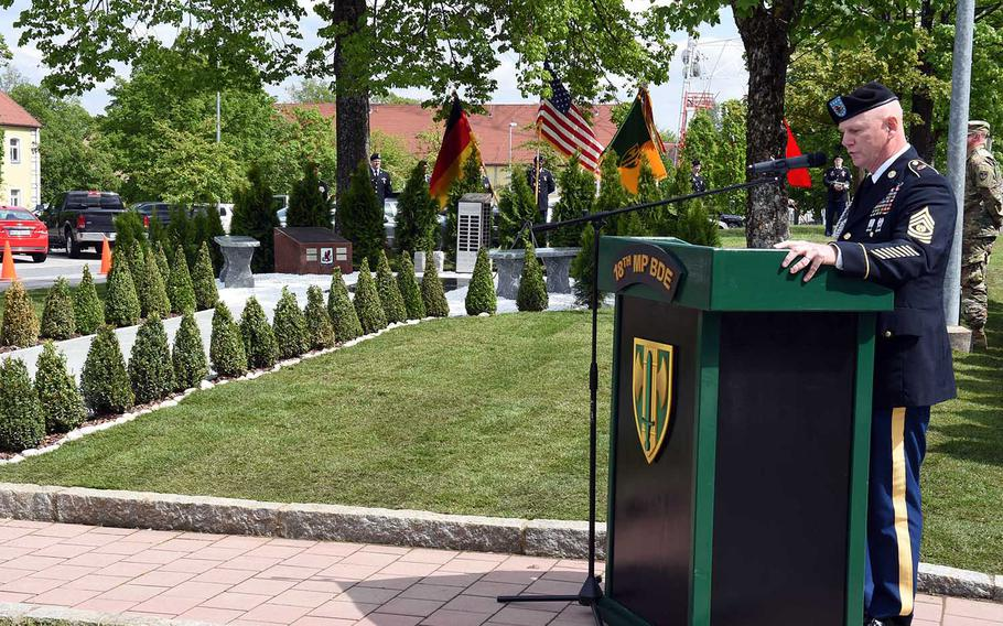 Sgt. Maj. Ted Pearson, with the 18th Military Police Brigade, speaks to his soldiers during a ceremony to rededicate a memorial to fallen soldiers from their brigade, Thursday, May 23, 2019, at Vilseck, Germany.