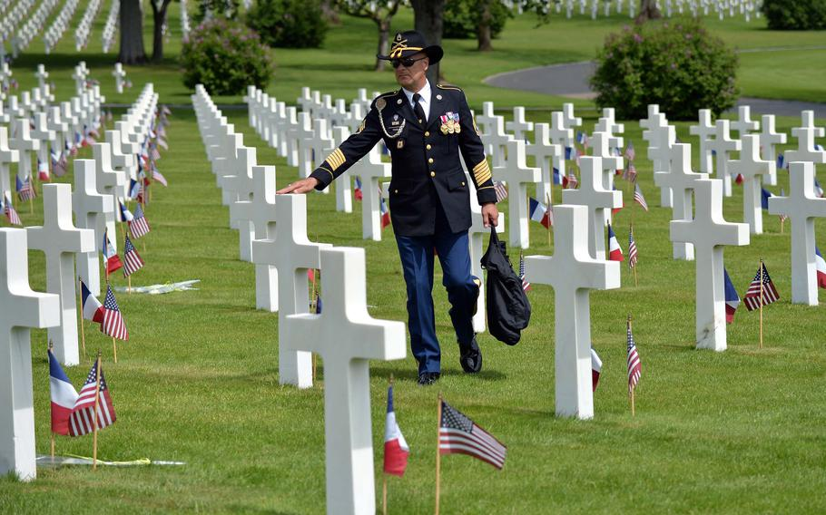 Retired Sgt. 1st Class Tom Favia touches a cross following a Memorial Day ceremony at Lorraine American Cemetery in St. Avold, France, Sunday, May 26, 2019. Favia, who lives nearby in Germany, says he tries to come to the ceremony every year. With 10,489 graves, the cemetery is the largest World War II U.S. World War II cemetery in Europe.