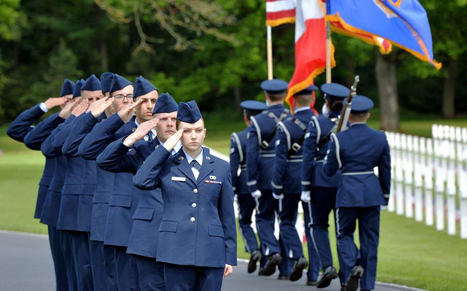 Airmen from Ramstein Air Base, who presented wreaths during the Memorial Day Ceremony at Lorraine American Cemetery, salute the color guard from the 52nd Fighter Wing out of Spangdahlem Air Base, as they march off the site at the conclusion of the ceremony.