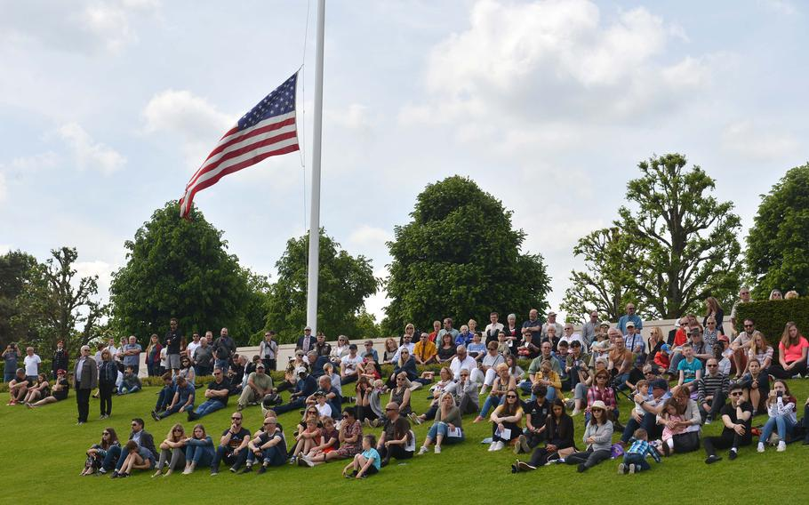Sitting under an American flag, people watch the Memorial Day ceremony at Lorraine American Cemetery in St. Avold, France, Sunday, May 26, 2019. Around 1,500 people attended the ceremony.